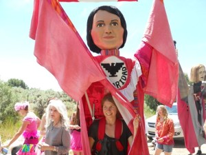 Rivera Sun carrying the giant Dolores Huerta puppet in Love-In-Action's Activists, Whistleblowers, and Muckrakers procession. Puppet built by Jeanne Green and Marilyn Hoff. Photo by Dariel Garner