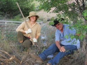 Peter Harris and Rivera Sun listen to the sound of the acequia (irrigation ditch) flowing sweetly toward Peter's field. Photo by Dariel Garner
